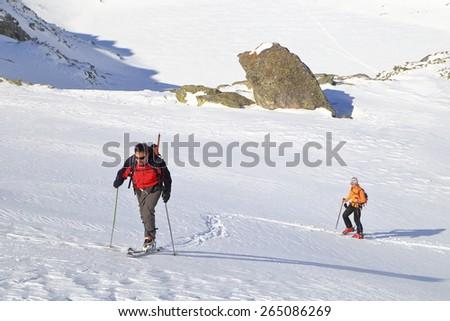 Ski mountaineers ascending on sunny white slope - stock photo