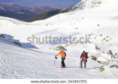 Ski mountaineers climbing uphill in fine winter day - stock photo