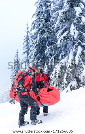 Ski patrol carry injured person skier in rescue stretcher snow - stock photo