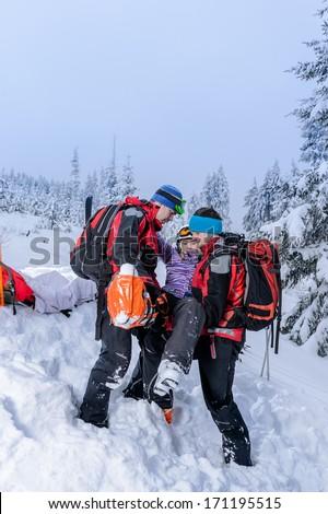 Ski patrol carry injured woman skier on rescue stretcher - stock photo