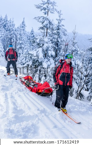 Ski patrol members carry injured skier downhill rescue stretcher - stock photo