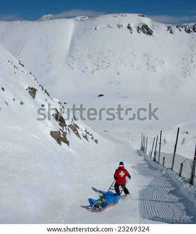 Ski patrol transporting an injured skier. Lake Louise Ski Resort, Alberta, Canada. - stock photo