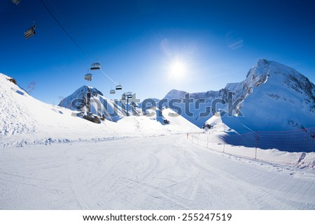 Ski piste panorama with ropeway chair lift  - stock photo