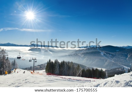 ski resort in mountains under blue sky - stock photo
