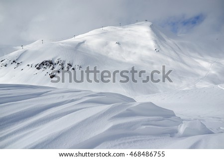 ski resort landscape, waves of fresh snow in the foreground and the slopes tracks in the background.