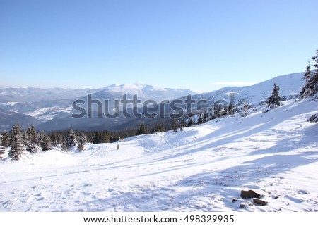 Ski resort. Mountain peaks and hills with trees sheltered snow.