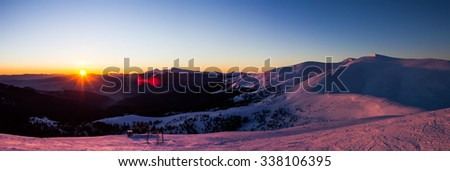 ski resort panorama in the morning when the sun rises and illuminates the snow-capped peaks - stock photo