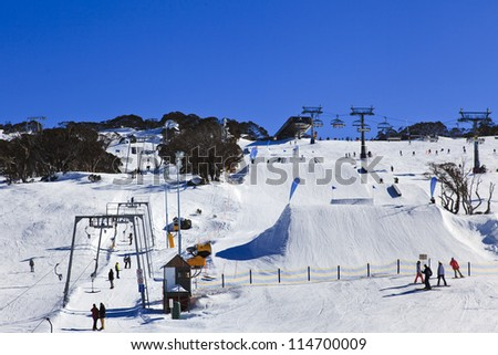 Ski resort winter season mountain slope with people sport skiing and snowboarding day time sunny weather - stock photo