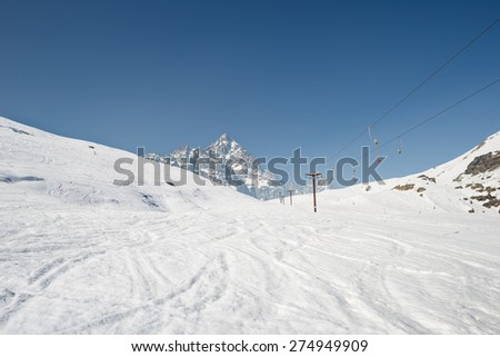 Ski resort with stunning view of high mountain peaks in the italian alpine arc, in a bright sunny day. Empty skilift in late season. - stock photo