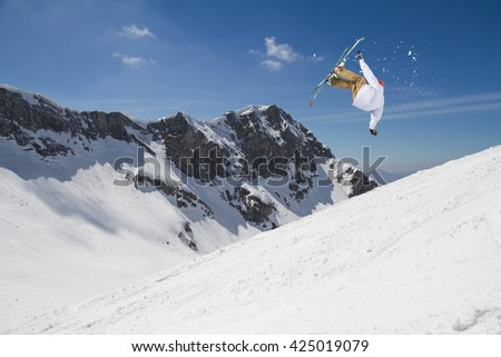 Ski rider jumping on snowy mountains. Extreme ski freeride sport. - stock photo