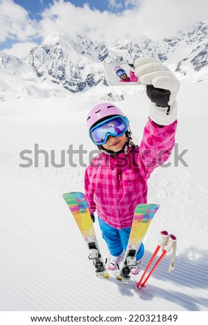 Ski, selfie, winter fun - lovely skier girl enjoying ski vacation - stock photo