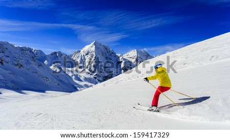 Ski, skier on ski run - woman skiing downhill, winter sport - stock photo