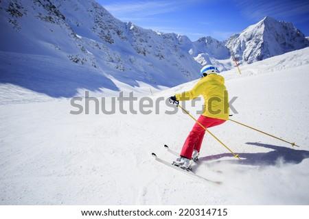 Ski, skier on ski run - woman skiing downhill, winter sport - stock photo