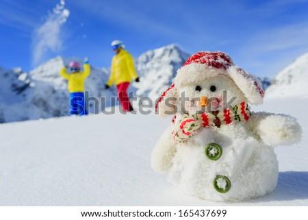 Ski, skier, sun and winter fun - skiers with snowman enjoying winter holidays - stock photo