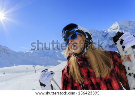 Ski, skier, sun and winter fun - young woman enjoying ski vacation - stock photo