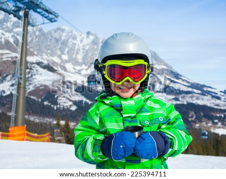 Ski, skier, winter. Lovely small boy has a fun on ski -  resting and drinking tea from a thermos. - stock photo