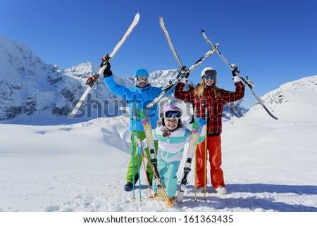 Ski, skiers, sun and fun - family enjoying winter vacation - stock photo