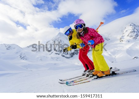 Ski, skiers, sun and winter fun - skiers enjoying ski vacation - stock photo