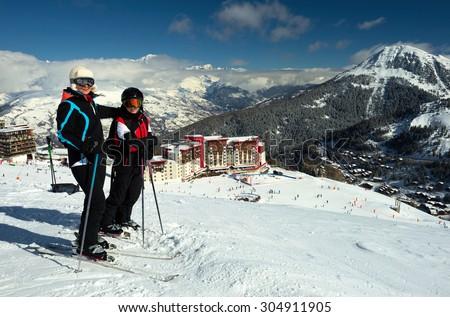 Ski, skiers, sun and winter fun - skiers enjoying ski vacation. Alpine Hotel. France. Travel - stock photo
