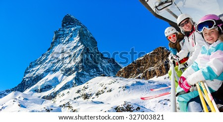 Ski, skiing in Zermatt, Switzerland - skiers on ski lift with view of Matterhorn  - stock photo