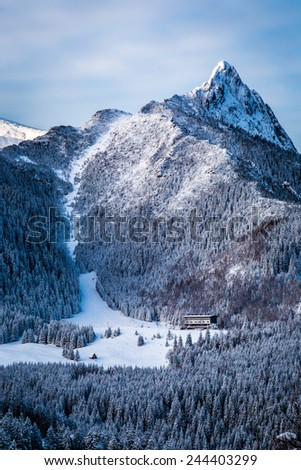 Ski slope at the foot of the mountains in winter - stock photo