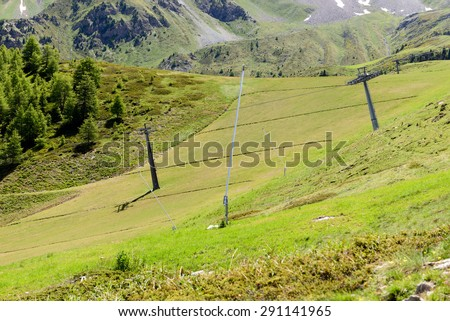 Ski slope in summer with snow cannons and pylons of the chairlift - stock photo