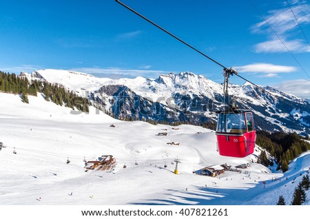ski slope in Swiss Alps in sunny day. Red cable car above and mountains behind, skiing resort, Switzerland. - stock photo