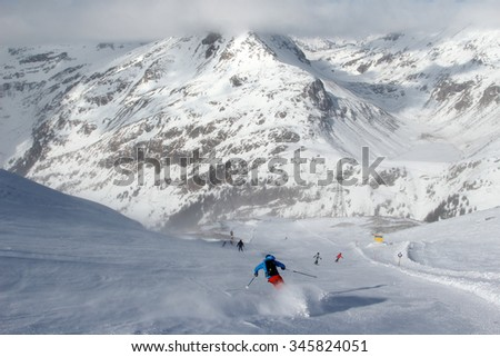Ski slope in the Austrian Alps with skiers - stock photo