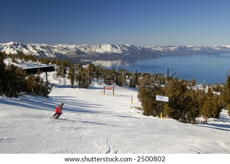 Ski slope motion blurred skier at lake Tahoe resort with the lake in the background. - stock photo