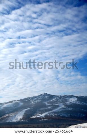 Ski slope under the light cloudy sky - stock photo