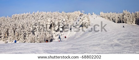 Ski slope with a lift in a snowy forest. Winter landscape. XXL panorama