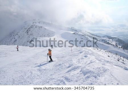Ski slope with skiers on ski resort Krvavec in Slovenian Alps - stock photo