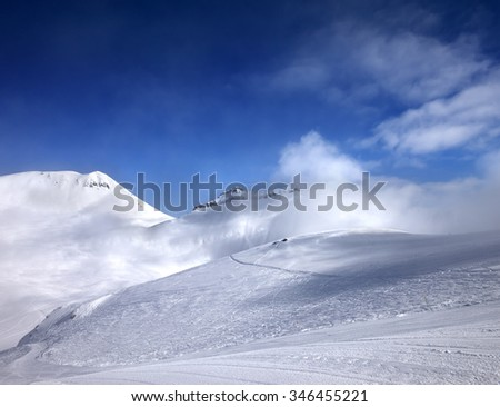 Ski slope with snowmobile trail and mountains in mist at nice day. Georgia, region Gudauri. Caucasus Mountains.  - stock photo