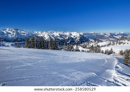 Ski slopes, Lake Lucerne and Swiss Alps covered by fresh new snow seen from the Spirstock peak in Hoch-Ybrig ski resort, Central Switzerland - stock photo