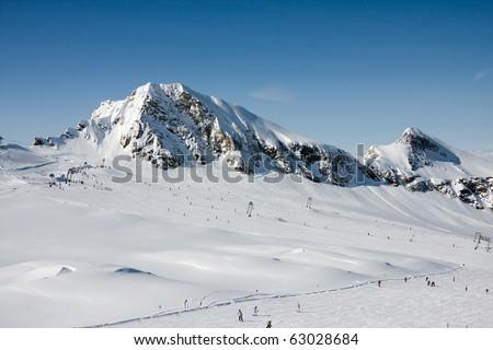 Ski slopes under high mountains in alp mountains - stock photo