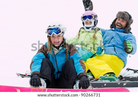 Ski, snow and fun - happy skiers playing in snow - stock photo