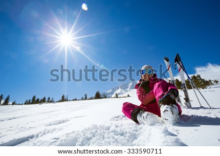 Ski, snow and sun - resting female skier in winter resort - stock photo