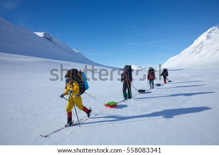 Ski touring group in colorful cloths with backpacks and sleds (pulkas) with snow covered mountains in the background. Cross country skiing in northern Sweden, beyond the Arctic Circle.