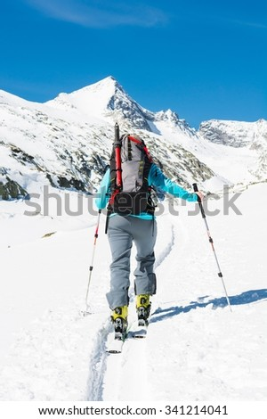 Ski touring in sunny weather. Female skier ascending a trail.