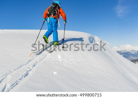 Ski touring man reaching the top at sunny day in Swiss Alps.