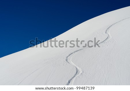 Ski trace in the snow with blue sky - stock photo