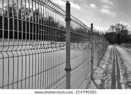 Ski track along the transparent metal fence in perspective after freezing rain in soft low backlit sunlight and harsh texture frosty snow (black and white) - stock photo