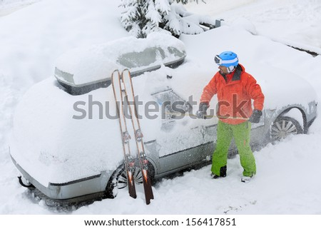 Ski, Winter, snow, car - skier man is shoveling the car of snow - stock photo
