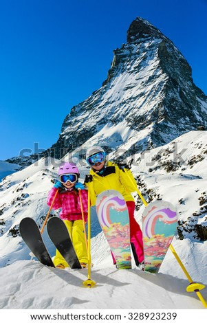 Ski, winter, snow - skiers enjoying winter vacation in Swiss Alps, mountain view Matterhorn - stock photo