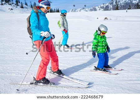 Ski, winter, snow, skiers, sun and fun - Mother teaches her children to ski on the winter vacations. - stock photo