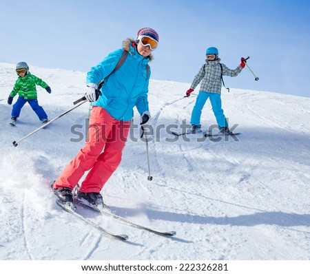 Ski, winter, snow, skiers, sun and fun - Mother with two happy kids enjoying winter vacations. - stock photo