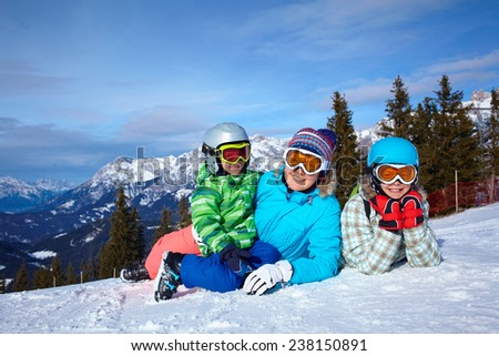 Ski, winter, snow, skiers, sun and fun - Two happy kids with mother enjoying winter vacations. - stock photo