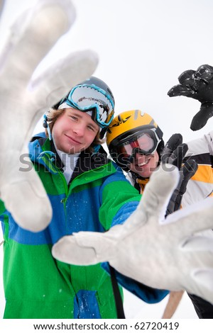 Skier and snowboarder in the snow posing for the camera - stock photo