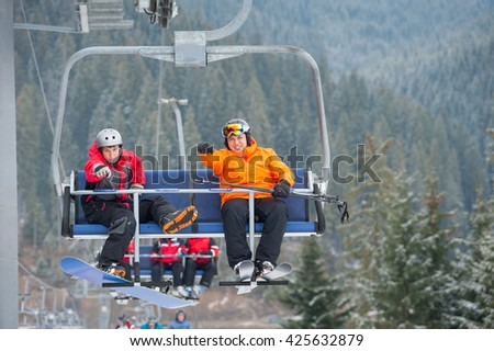Skier and snowboarder riding up to the top of the mountain on ski lift, with an astonishing view nature - stock photo