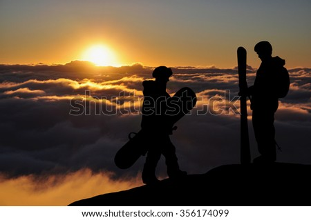 Skier and snowboarder silhouette high above the clouds in mountains. Snowboarder walking to the standing skier during a sunset, colorful sky in front of them. Couple of freeriders on the hill. - stock photo